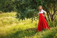 穿着红色裙子的妇女站立在树下 免版税库存照片