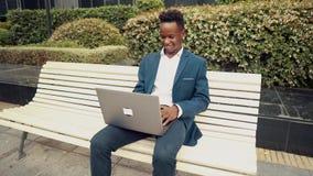 穿着蓝色衣服的非裔美国人的商人藏品膝上型计算机笔记本 影视素材
