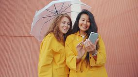 穿着雨衣、在户外用智能手机撑伞的快乐年轻女性 影视素材