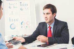 穿着黑衣服的年轻商人微笑在会议 免版税库存图片