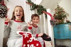 穿睡衣的两个激动的孩子画象坐拿着长袜的台阶在圣诞节早晨 库存图片