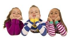 穿睡衣的美丽的幼儿倾斜在他们的手肘 免版税库存图片