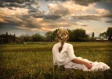 穿礼服的女孩坐在牧场地 库存图片