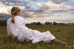 穿礼服的女孩坐在牧场地 免版税库存图片
