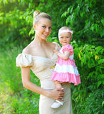穿礼服的愉快的年轻母亲和小女儿画象  图库摄影