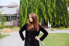 穿空白的黑T恤杉、牛仔裤和外套的女孩生活方式画象摆在反对用绿色叶子盖的大厦 免版税库存图片