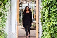 穿空白的黑T恤杉、牛仔裤和外套的女孩生活方式画象摆在反对用绿色叶子盖的大厦 图库摄影