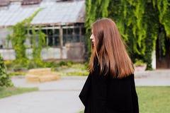穿空白的黑T恤杉、牛仔裤和外套的女孩生活方式画象摆在反对用绿色叶子盖的大厦 库存照片