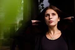 穿空白的黑T恤杉、牛仔裤和外套的女孩生活方式画象摆在反对用绿色叶子盖的大厦 免版税库存照片