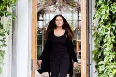 穿空白的黑T恤杉、牛仔裤和外套的女孩生活方式画象摆在反对用绿色叶子盖的大厦 库存图片