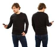 穿空白的黑衬衣的人拿着电话 免版税图库摄影