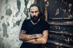 穿空白的T恤杉的残酷有胡子的人画象  免版税库存照片