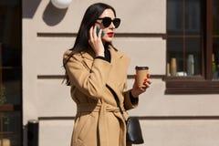 穿米黄外套和拿着外带的咖啡的可爱的繁忙的妇女画象,当谈话在电话,谈论重要时 免版税库存照片