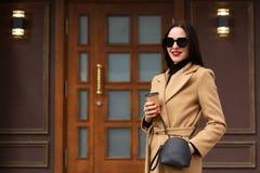 穿米黄外套,黑毛线衣的快乐的年轻女人,有提包,并且太阳镜,喝在纸杯的外带的咖啡,摆在 库存照片