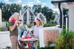 穿米黄长裤的快乐的有胡子的成熟人来到庭院旧货出售 免版税库存照片