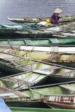 穿紫色衬衣的妇女,圆锥形帽子运载桨,并且席子,坐有许多小船的一条小船停止在河在的Trang 免版税库存照片
