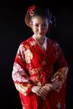 穿红色和服的年轻俏丽的妇女 免版税库存照片