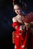 穿红色和服的年轻俏丽的妇女 免版税库存图片