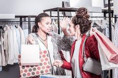 穿红色外套的深色头发的妇女谈话与她的最好的朋友在购物以后 库存照片