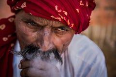 穿红色头巾的人抽烟的水烟筒 免版税图库摄影