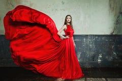穿红色晚礼服的美丽的时尚女孩 免版税库存照片