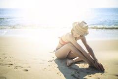 穿红色比基尼泳装的女孩坐海滩 免版税库存图片