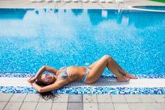 穿红色比基尼泳装的美好的女性时装模特儿休息在水池边缘在豪华旅游胜地 年轻白种人夫人sunbathin 库存图片