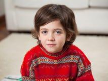 穿红色毛线衣的男孩在圣诞节期间 库存照片