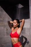 穿红色泳装的一名年轻性感的妇女淋浴外部在豪华旅馆 免版税库存照片