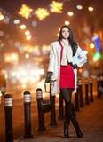 穿红色礼服和白色外套的时兴的夫人室外在与城市的都市风景在背景中点燃。全长画象 库存照片