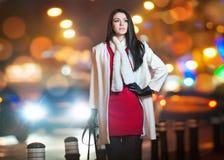 穿红色礼服和白色外套的时兴的夫人室外在与城市的都市风景在背景中点燃。全长画象 免版税库存照片