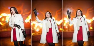 穿红色礼服和白色外套的时兴的夫人室外在与城市的都市风景在背景中点燃 全长纵向 免版税库存照片