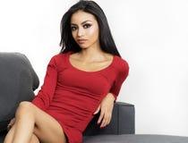 穿红色礼服的美丽的妇女坐黑椅子 图库摄影
