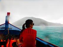 穿红色衬衣的亚洲妇女坐longtail小船,当雨时 库存图片
