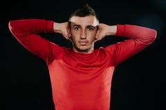 穿红色运动服和摆在黑暗的背景的坚硬锻炼以后的英俊的欧洲运动员 舒展与h的运动的人 免版税库存图片
