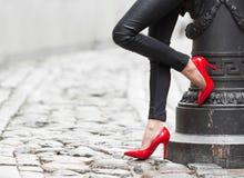 穿红色高跟鞋鞋子的性感的妇女在城市 库存照片
