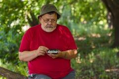 穿红色T恤杉的老人认为在接下来的步骤,当打迷你棋时 免版税库存图片