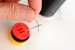 穿线与黑螺纹的手一根针 库存图片
