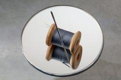 穿线卷轴和针在一个圆的镜子 库存图片