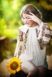 穿罗马尼亚传统女衬衫的女孩拿着向日葵室外射击。美丽的白肤金发的女孩画象  库存照片