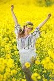 穿罗马尼亚传统女衬衫的女孩摆在油菜领域,室外射击 美丽的金发碧眼的女人画象有花圈的 库存照片