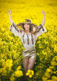 穿罗马尼亚传统女衬衫的女孩摆在油菜领域,室外射击 美丽的金发碧眼的女人画象有草帽的 免版税库存图片