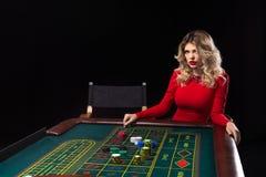 穿美丽的红色礼服的年轻白肤金发的妇女在赌博娱乐场演奏轮盘赌 免版税库存照片