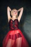 穿美丽的长的红色裙子和束腰的白肤金发的妇女 免版税图库摄影