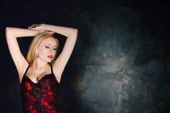 穿美丽的长的红色裙子和束腰的白肤金发的妇女 图库摄影
