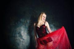 穿美丽的长的红色裙子和束腰的白肤金发的妇女 免版税库存图片