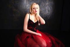 穿美丽的长的红色裙子和束腰的白肤金发的妇女 库存图片