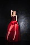 穿美丽的长的红色裙子和束腰的白肤金发的妇女 免版税库存照片
