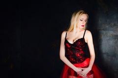 穿美丽的长的红色裙子和束腰的白肤金发的妇女 库存照片
