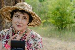 穿草帽的妇女,使用她的唇膏本质上 免版税库存图片